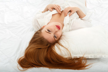 Portrait of a beautiful sexy girl lying in bed in a man's shirt