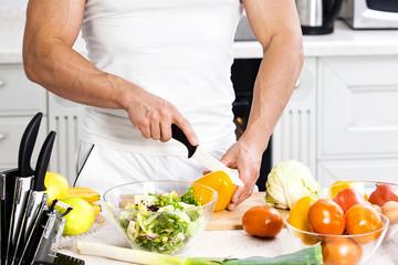 Handsome man cooking at home preparing salad in kitchen.