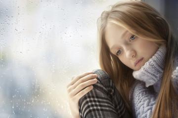 Rainy Day: sad Girl on the Window