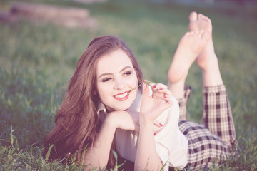 Young Romantic Woman Sitting on the Grass