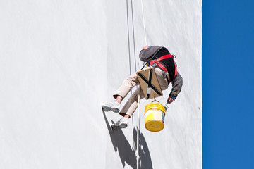 Maler Seilt sich zum Streichen einer Wand ab