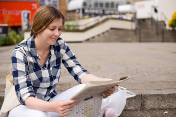 young woman reading the newspaper outdoors