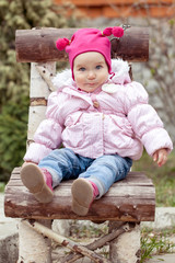 baby girl in pink jacket sitting on wooden chair
