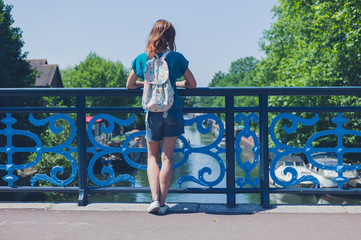 Young woman standing on bridge looking at canal