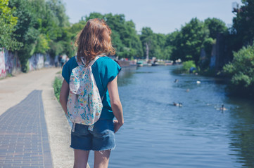 Young woman standing by canal