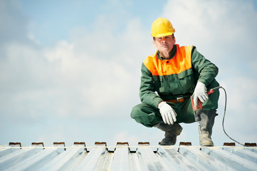 Worker builder roofer at metal profile work