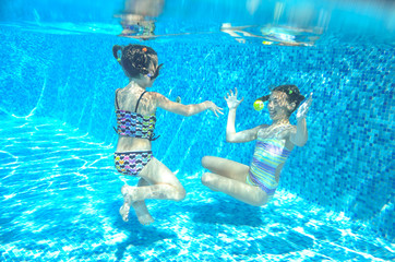 Happy children swim in pool underwater, girls swimming, playing and having fun