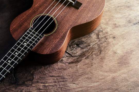 Close up of ukulele on old wood background with soft light