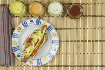 Domestic hot-dog with vegetables, fast food preparation at home.