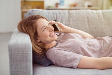 frau liegt auf dem sofa und telefoniert