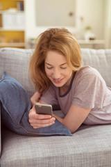 mädchen liegt auf dem sofa und schaut auf ihr mobiltelefon