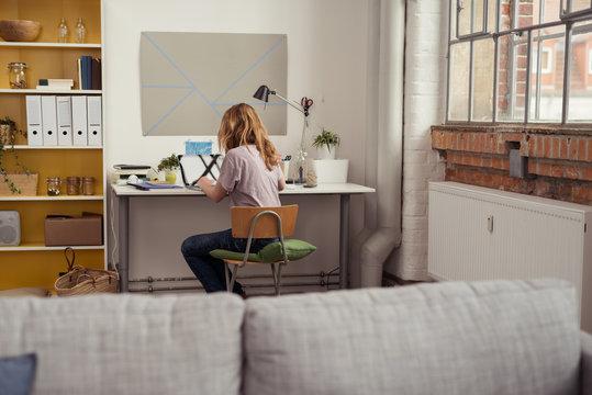 studentin sitzt zuhause am schreibtisch und arbeitet am laptop