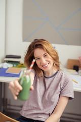 studentin am schreibtisch trinkt einen grünen smoothie