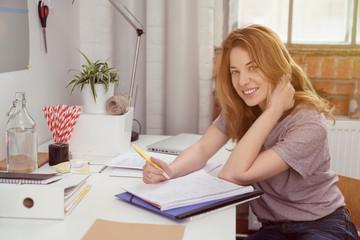 studentin schreibt zuhause am schreibtisch