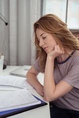 studentin lernt konzentriert zuhause am schreibtisch