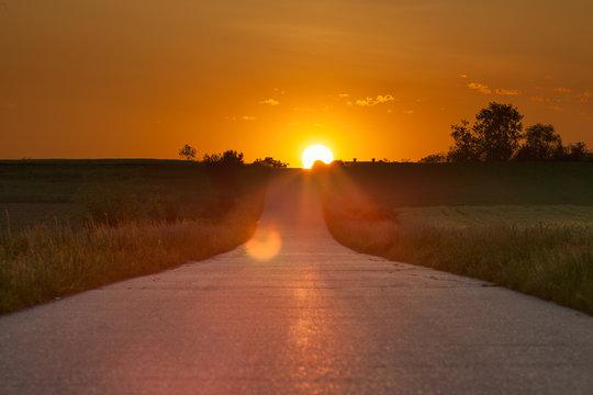 Driving on an asphalt road towards the setting sun