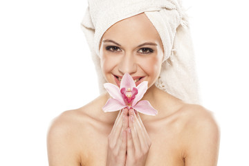 smiling woman with orchid and towel on her head posing on white