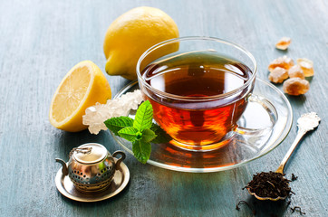 Wall Mural - Cup of black tea with mint, lemon and chrystal sugar