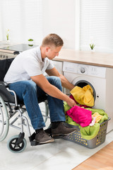 Disabled Man Putting Towels Into The Washing Machine