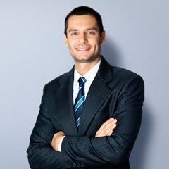 Happy smiling businessman with crossed arms, over grey