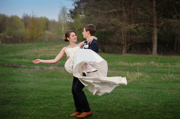 Happy bride and groom walking on the edge of a pine forest in the spring