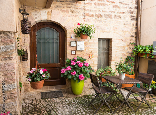 Ingresso romantico di casa con mobili da giardino e vasi for Foto case con giardino