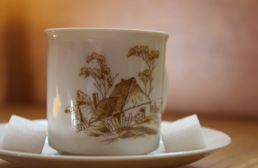 painted china tea cup with pattern of countryside house, with cubes of sugar