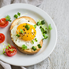 Foto op Canvas Gebakken Eieren toast with fried egg and tomatoes on a light wooden background