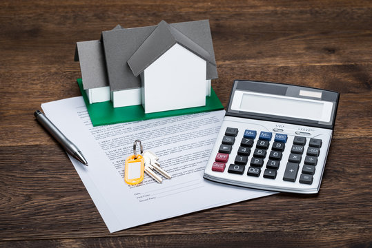 House Model On Contract Paper With Keys And Calculator
