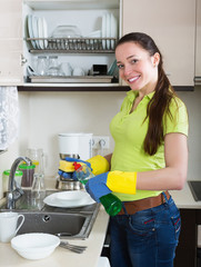 Smiling young housewife washing dishes
