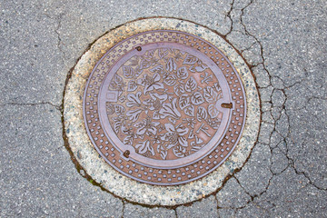 Drain cap art on the surface of sewer cover on the walk way takayama japan