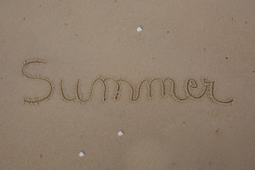 The  word summer written in a sand