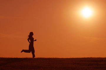 Silhouette of girl jogging in the sunset
