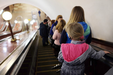 The girl in headphones on the escalator in the metro