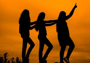 three silhouettes of girls against the sky at sunset,dancing