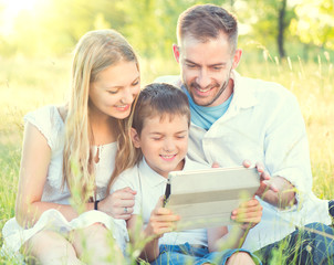 Happy young family with kid using tablet PC in summer park
