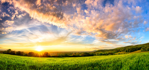 Photo sur Aluminium Lavende Panorama of a colourful sunset on a green meadow