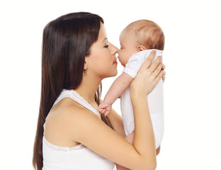 Portrait of young loving mother kissing cute baby
