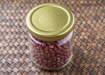 Red adzuki beans in a mason jar over wicker background