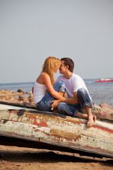 couple sitting on old boat and kiss