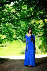 beautiful princess in shadow of big trees