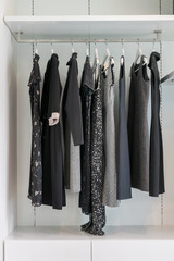 modern closet with row of black dress hanging on coat hanger in