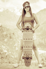 Vintage image of hippie young and beautiful girl with skateboard