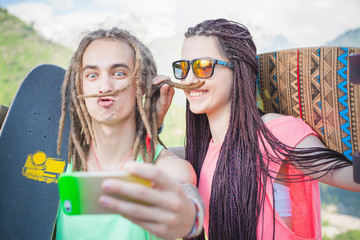 Couple make selfie on mobile phone, making mustache of hair