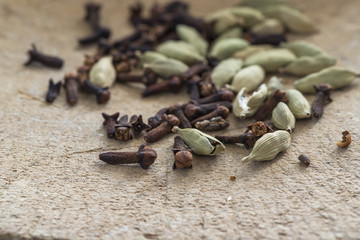 Cardamom seeds and cloves - closeup with selective focus