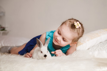 Cute little girl playing with white rabbits