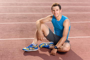 Smiling sportsman sitting and having rest