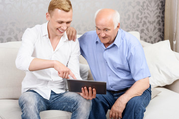 Grandfather and grandson using tablet together
