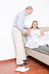Krankenpfleger hilft Frau beim Aufstehen