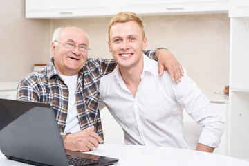 Grandfather and grandson sitting with laptop